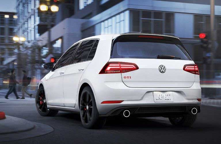 Rear driver angle of a white 2019 Volkswagen Golf GTI driving in a city