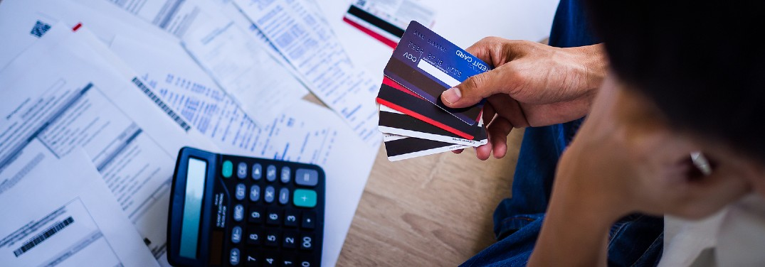 Woman holding credit cards while looking at finance papers and a calculator