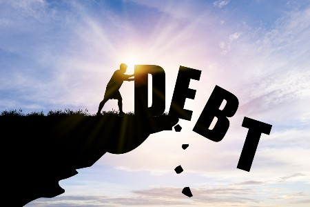 """Graphic showing a man pushing the letters that spell """"Debt"""" off a cliff"""