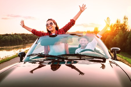 Happy couple driving a convertible vehicle on a sunny day