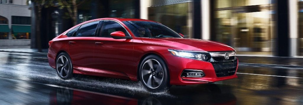 Front passenger angle of a red 2020 Honda Accord driving on a wet road