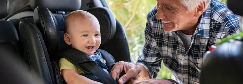 Grandfather buckling a baby boy into a car seat