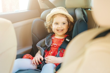 Happy girl sitting in a car seat