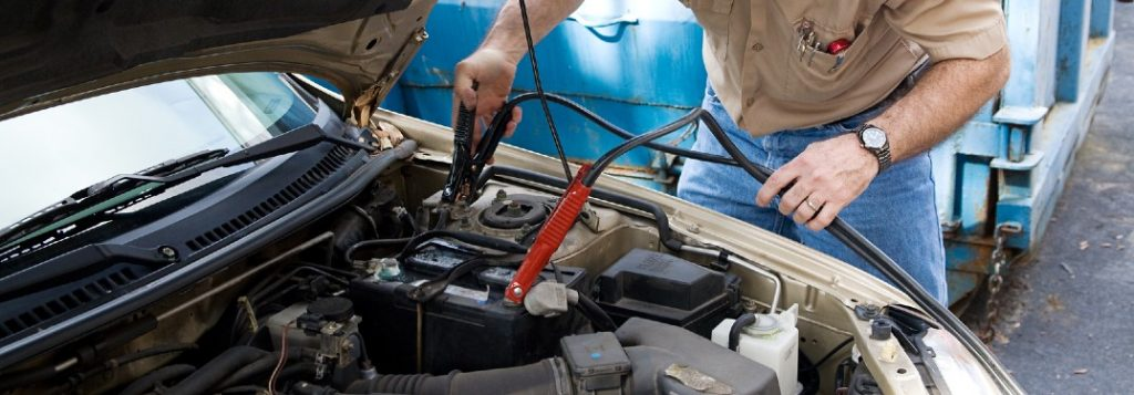 Close up of a mechanic jump starting a car battery