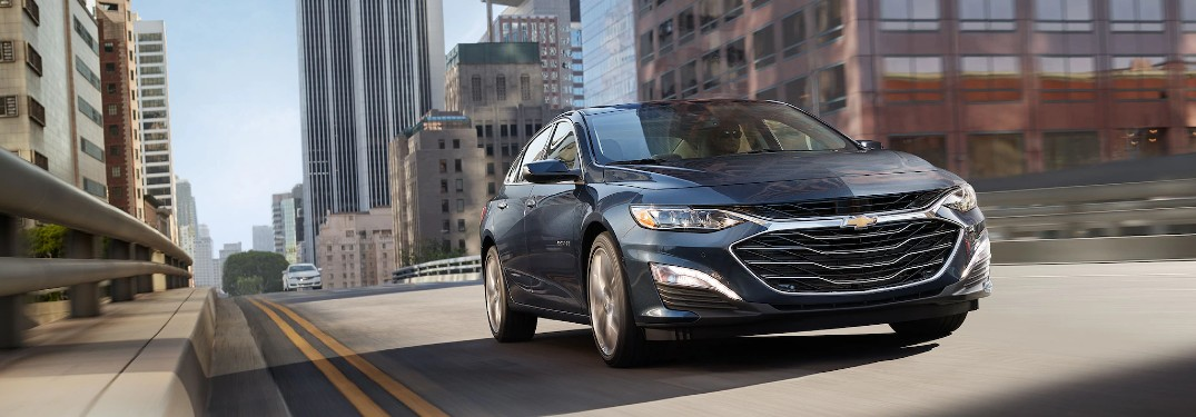 Front passenger angle of a grey 2020 Chevrolet Malibu driving in a city