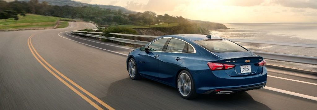 Rear driver angle of a blue 2020 Chevrolet Malibu driving by the ocean
