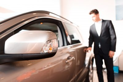 Man inspecting a vehicle in a dealership