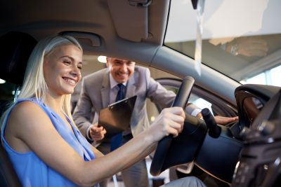 blonde woman sitting in a car looking at the dashboard with a sales man pointing