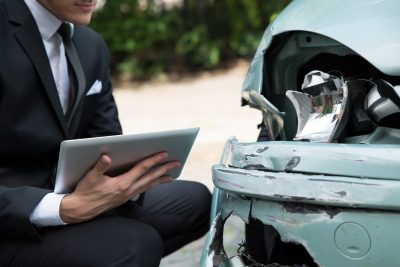 man in a suit examining a vehicle that had been in a collision