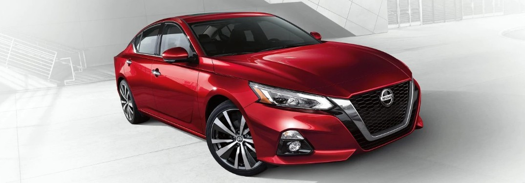 Front passenger angle of a red 2020 Nissan Altima on a white and grey background