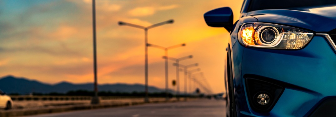 Close up of a blue car driving on a road with a sunset in the background