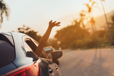 Car driving on a road in the summer with a person's hand out of the window