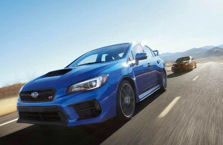 Front driver angle of a blue 2020 Subaru WRX with a red 2020 Subaru WRX driving behind it