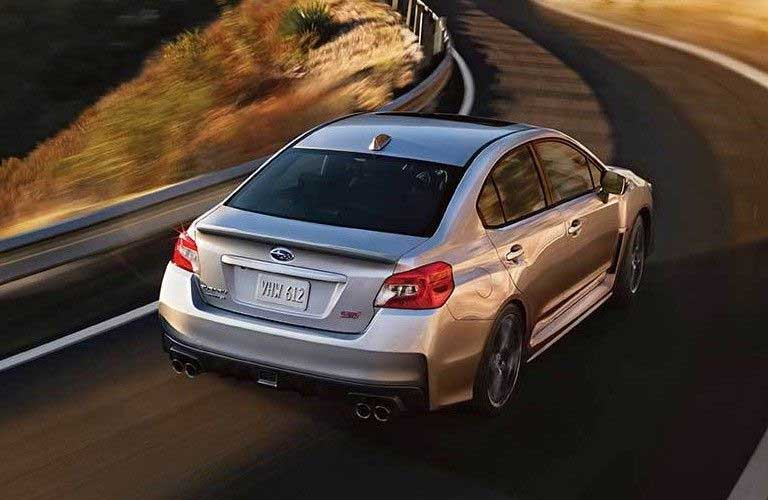 Rear passenger angle of a silver 2020 Subaru WRX driving on a curvy road