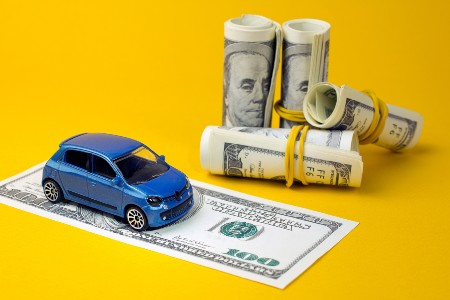 Blue toy car on top of a one-hundred dollar bill with other bills rolled up next to it