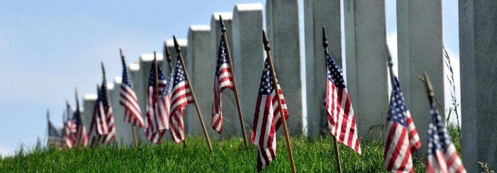 Gravestones lined up with American flags in front of them