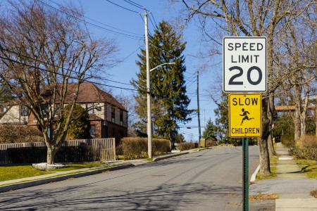 """Speed limit sign with a """"Slow Children"""" sign below it"""