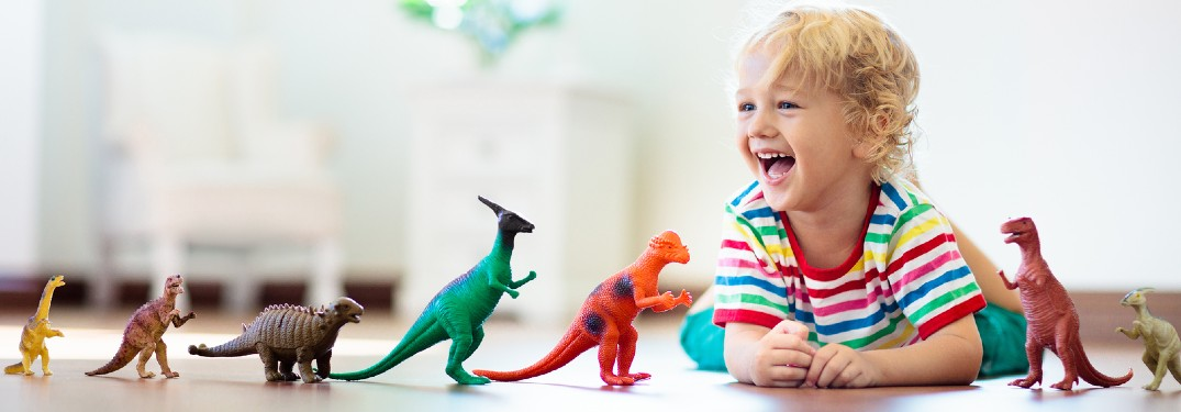 Happy boy with toy dinosaurs