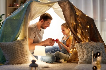 Happy father and daughter inside of a blanket fort