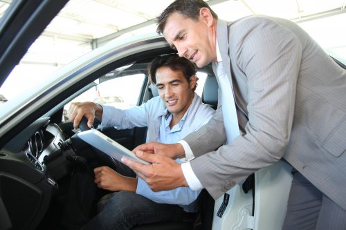 A man and a car dealer looking a paperworkd