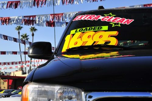 Used truck with brightly colored window stickers reading ultra clean, loaded and 16995 with streamers over head
