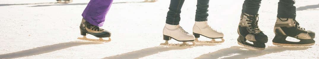 Three pairs of skates on an outdoor ice rink