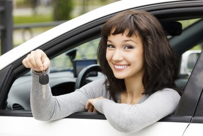 Young woman holding the keys to a car sitting in the drivers seat