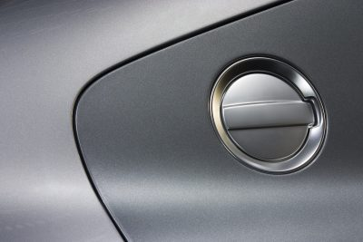Closeup of a silver vehicle with a closed gas cap