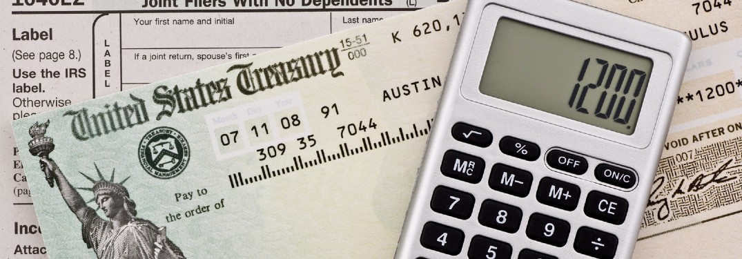 Close up of a US Treasury stimulus check with a calculator displaying 1200