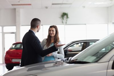 Woman looking for a car in a dealership talking to a salesperson