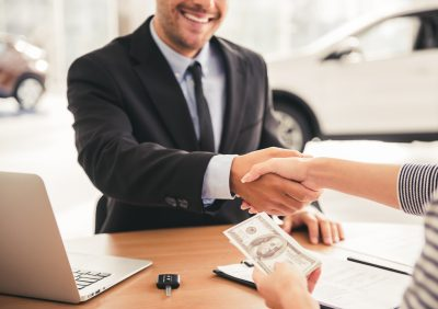 man and woman shaking hands while sitting at at desk in a car dealership as the woman hands over a $100 bill
