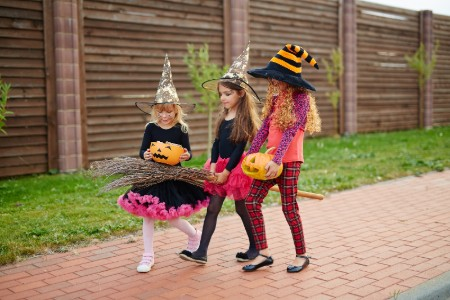 Three young girls dressed up as witches for Halloween and trick or treating