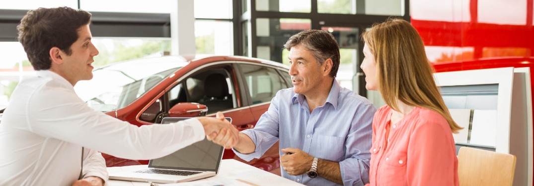 Couple shaking hands with a salesman after buying a car
