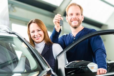 Happy couple holding car keys by a car