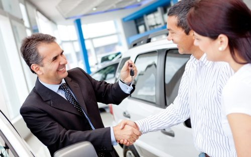 Sales man and couple shaking hands while the salesman hands them a key for a vehicle