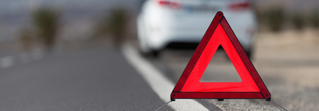 Close up of an orange reflective triangle with a white car pulled over in the background