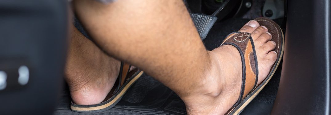 Close up right foot with flip flop shoe step on the accelerator in the modern car