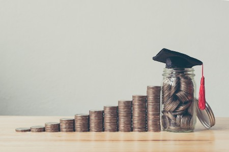 Coins stacked up with a small jar of coins and a graduation cap on top