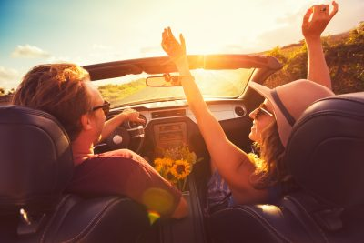 Two people driving on an open highway in a convertible with the woman raising her arms