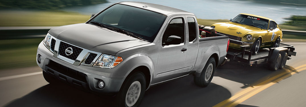Nissan Frontier towing trailer with a car on it