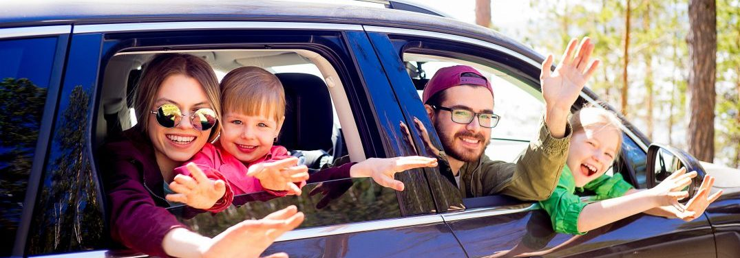 Family of four waving from the windows of a vehicle