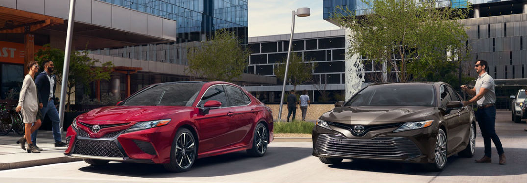Two Toyota Camry sedans parked by a building
