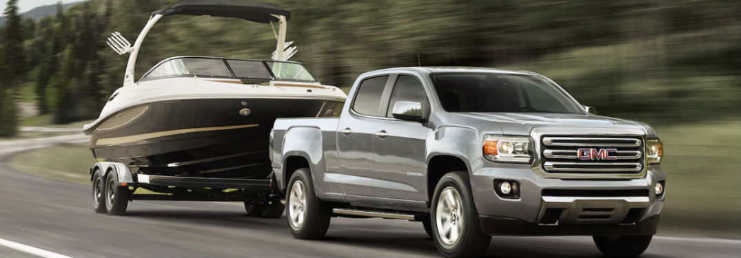 GMC Canyon towing a boat on a road