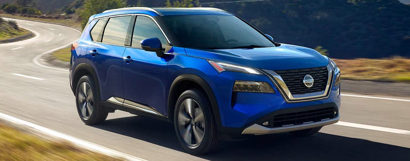 A blue 2021 Nissan Rogue is driving on a winding road.