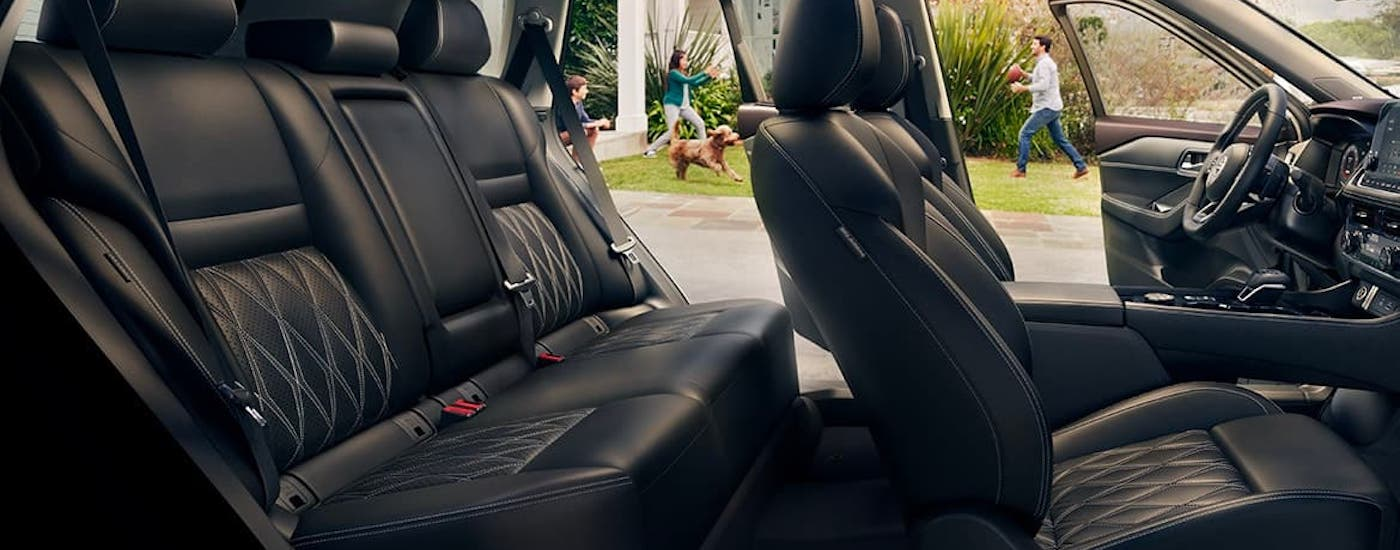 The black interior and rows of seats inside a 2021 Nissan Rogue are shown from the side.