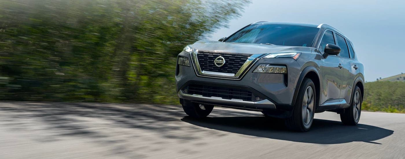 A gray 2021 Nissan Rogue is driving on a highway and shown from a low angle.