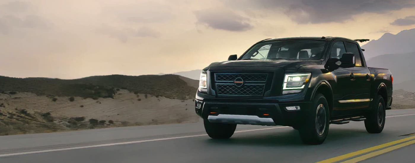 A black 2021 Nissan Titan is driving on a highway at dusk with mountains in the distance.