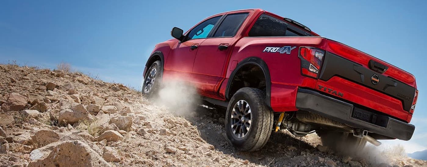 A red 2021 Nissan Titan Pro4x is shown from the rear climbing a dirt hill.