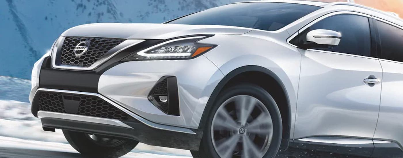 A white 2021 Nissan Murano is driving on a snowy road.