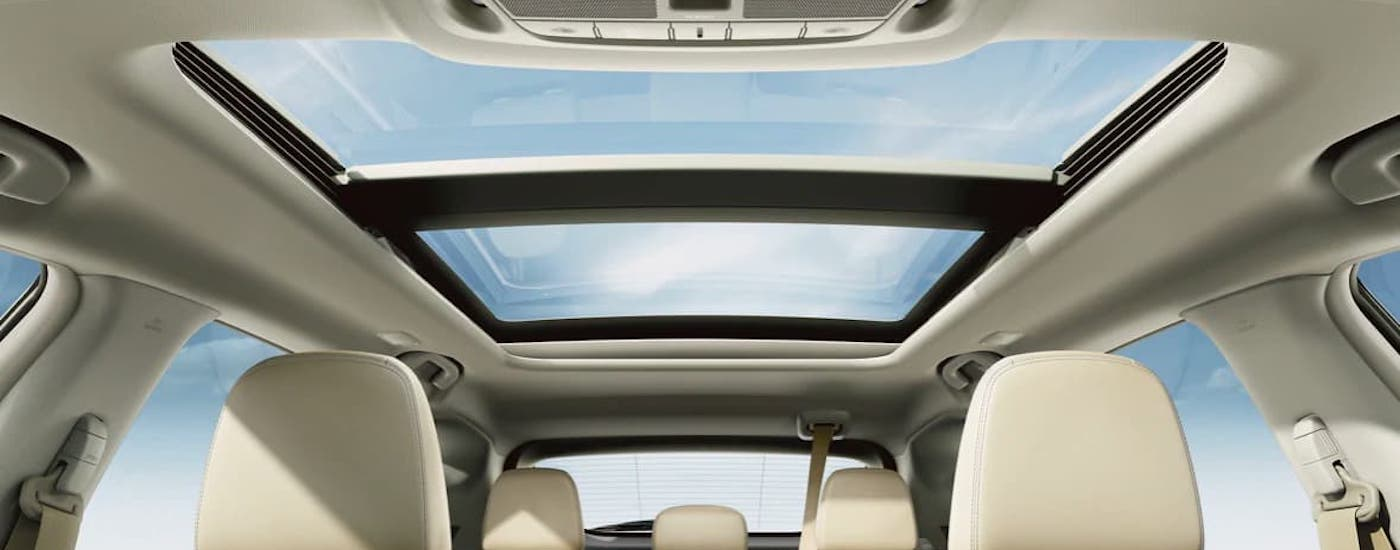 A view of the panoramic moonroof inside a 2021 Nissan Murano is shown from a low angle inside the cabin.